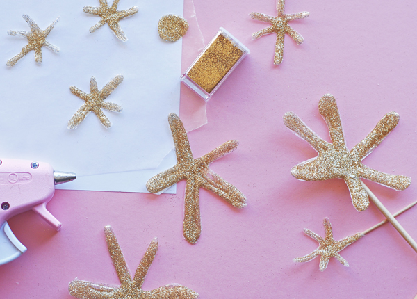 Make golden stars with hot glue and glitter.